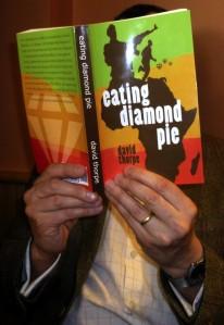 David Thorpe's face hidden behind his novel