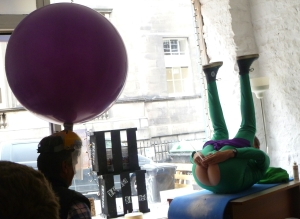 Mr Methane farts a dart at a balloon on a worried man's head