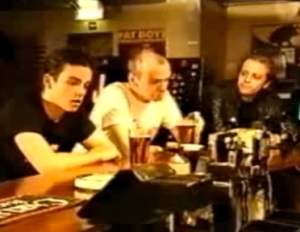 Robbie Williams (left) in the Newcy Brown video