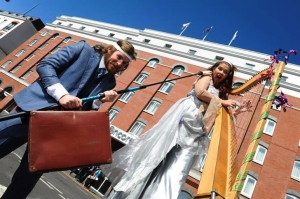 Ursula, on stilts, plays her harp in Belfast