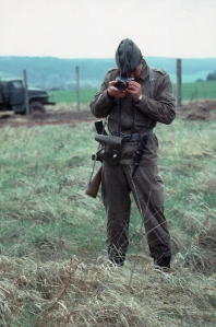 An East German GDR border scout apparently photographing grass along the border
