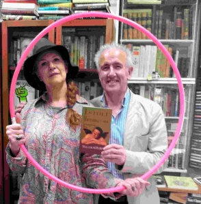 Anna Smith & Gordon Breslin (a visitor from South London who is irrelevant to this piece) hold a copy of dead comedian Malcolm Hardee's iconic autobiography (also irrelevant to this piece) within a hula hoop in Vancouver two weeks ago.