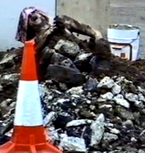 Ian Hinchliffe in mud & rubble outside Riverside Studios