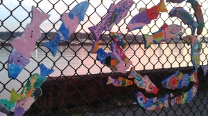 A salmon decoration by children on fence above Fraser River