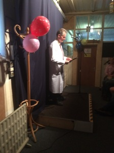 John Hatch reads the fire regulations to the audience amid birthday balloons